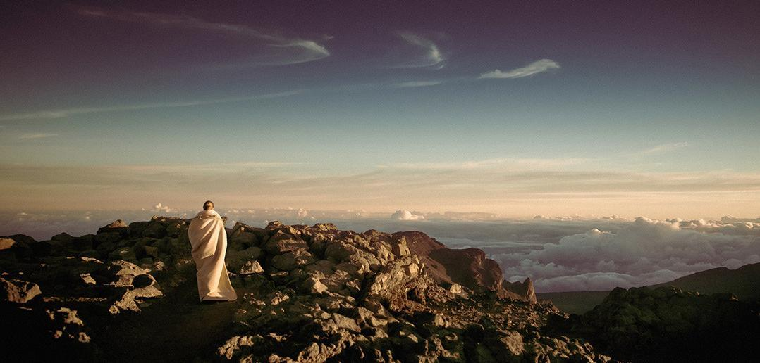 A person meditating, standing on a mountain peak, in front of the horizon.