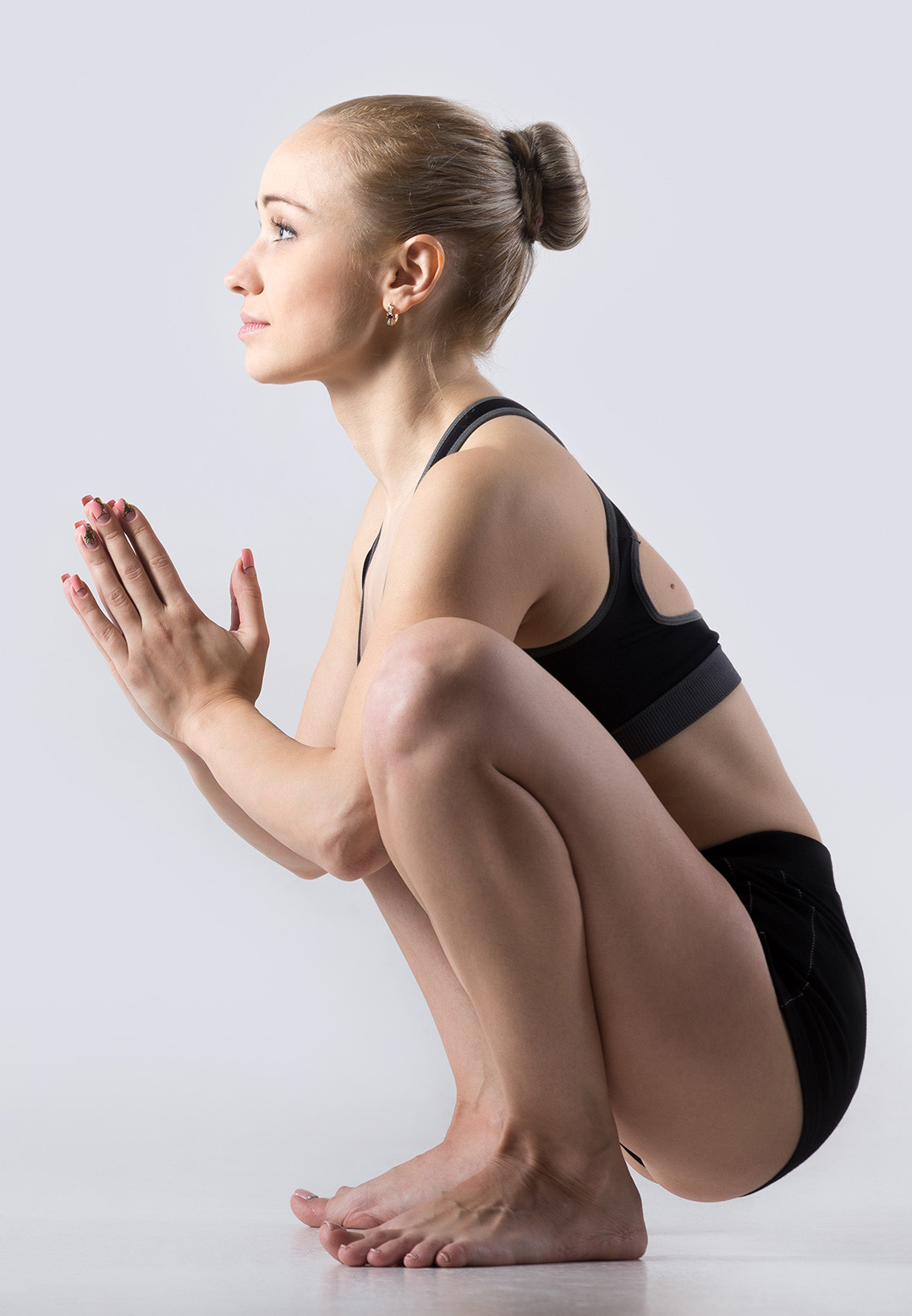 A side profile pic of a young woman sitting in a natural flat-footed squat position