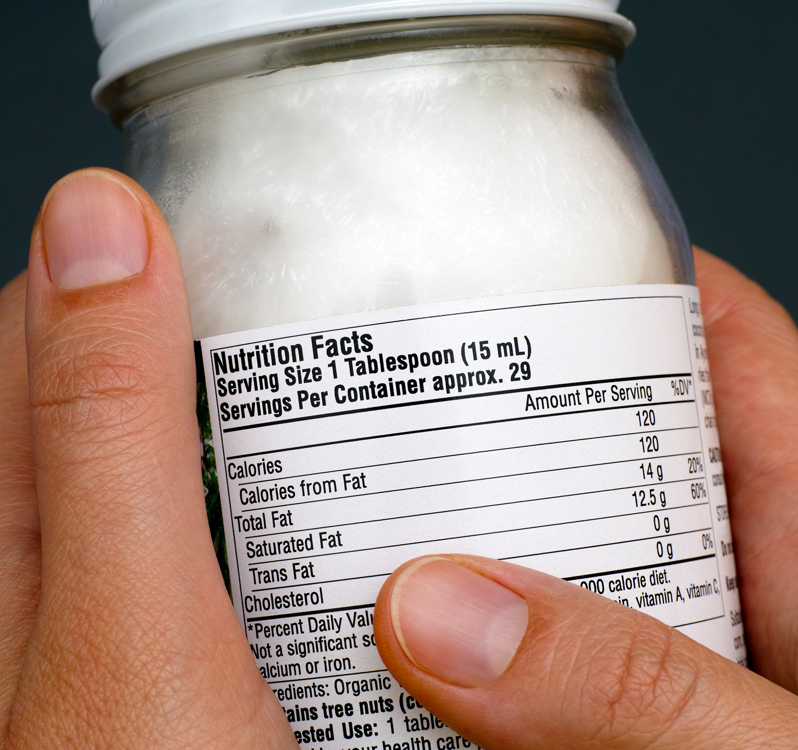 2 hands holding a coconut oil jar with the nutrition facts label on it.