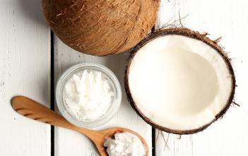 Perfectly white coconut oil in a glass bowl, with a raw fresh coconut split in half and a spoon next to it.