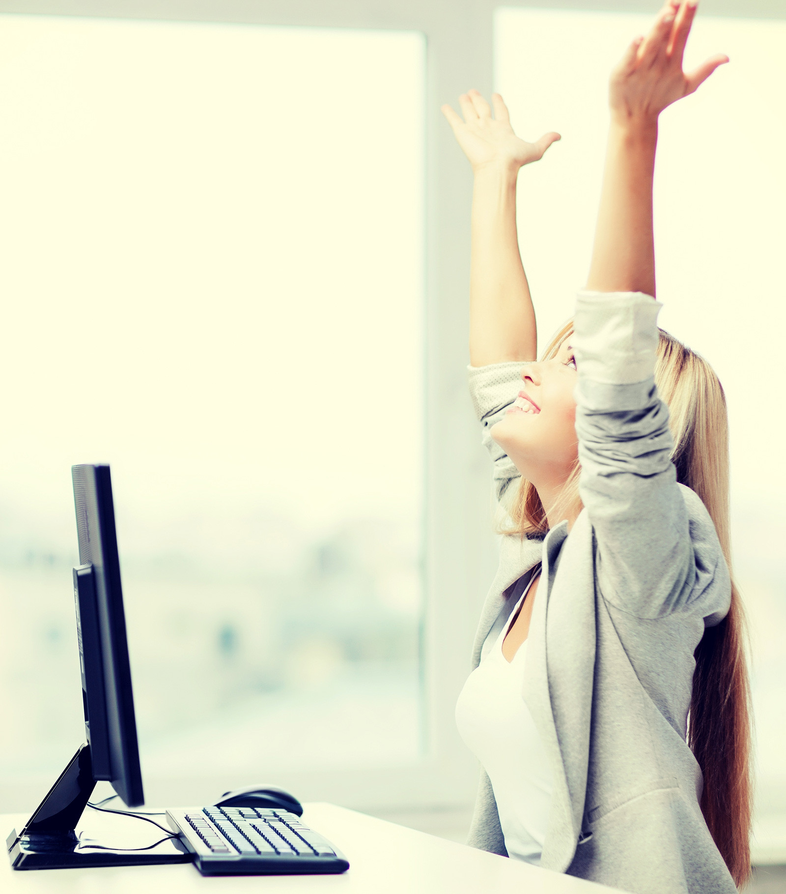 A female-employee raising her arms in the air out of joy.