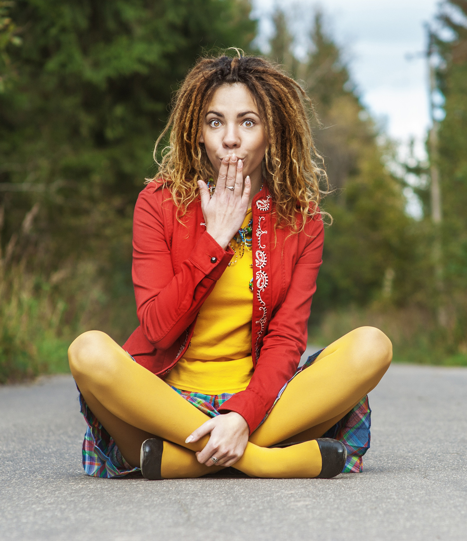 A young, colorful woman with dreadlocks in shock.
