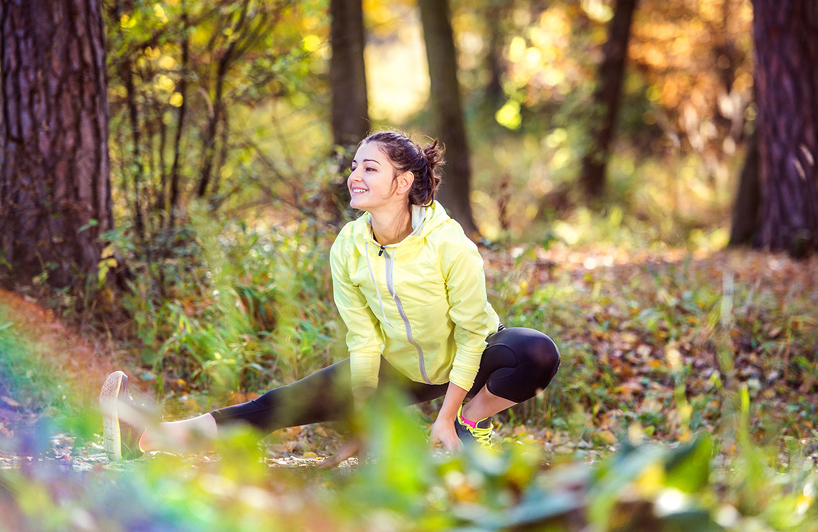 A young smiley woman stretching in the middle of nature.