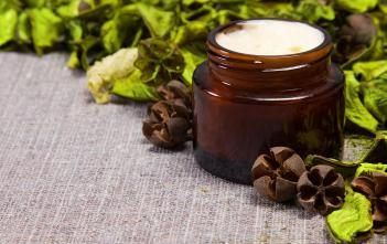Natural skin care cream in a jar, with green leaves next to it.