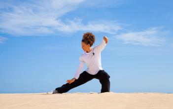 A woman practicing tai-chi in a natural environment.