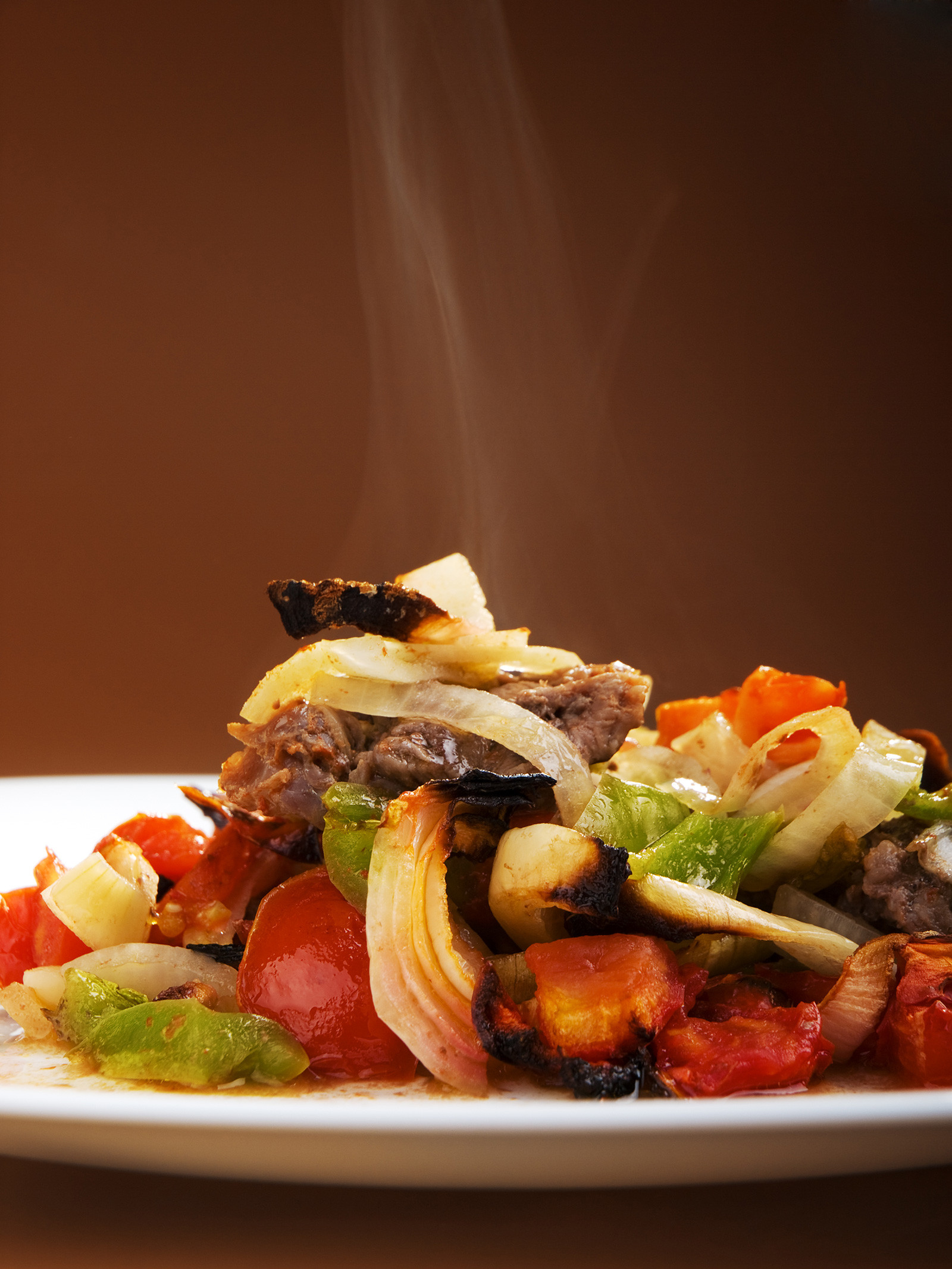 Beef stew with green peppers, onion and tomatoes, served in a plate, steaming