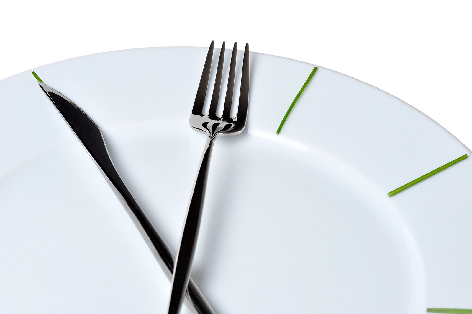 A fork and a knife laid on a round plate, forming the look of a clock