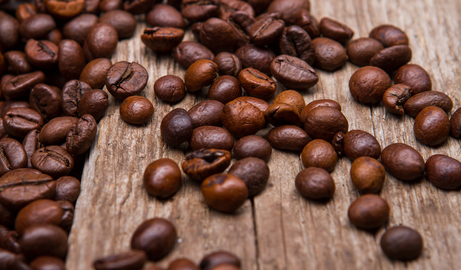 Coffee beans spread across table.