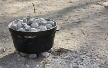 A Dutch oven with charcoal pieces on top of and beneath it.