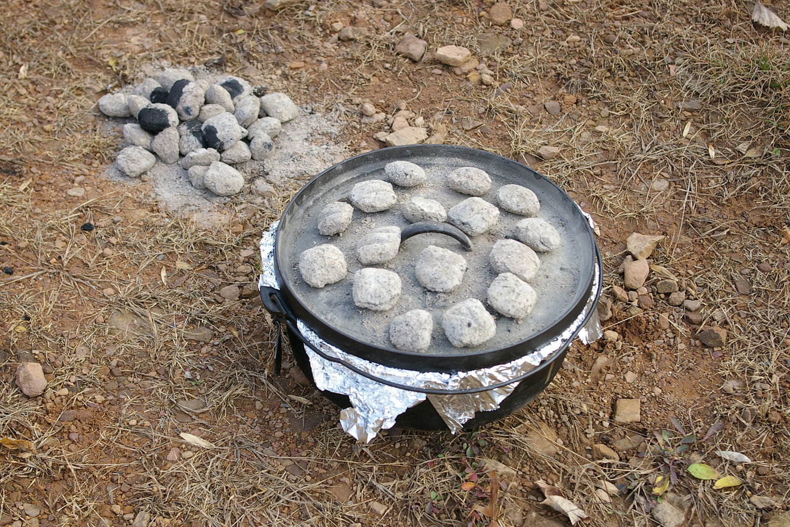 A Dutch-oven covered with tin-foil, a lid and charcoals, and other charcoals next to it.