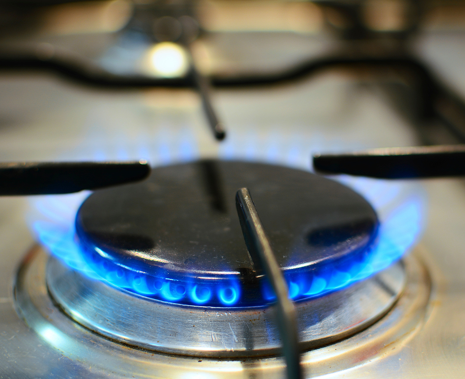 A gas stove burner turned on, creating a blue flame.