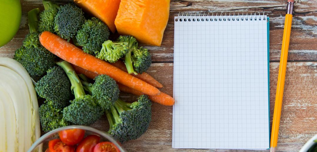 A notebook and a pencil surrounded by real food