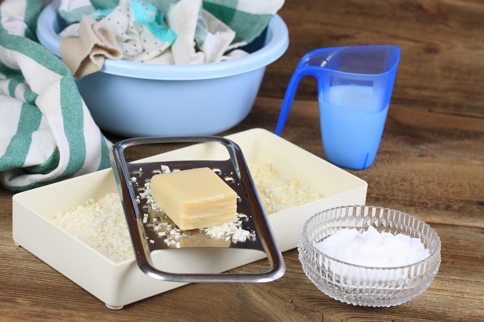 Soap and grated soap, crystalline-sodium in a bowl, and some clothes/cloths in a shallow bucket.