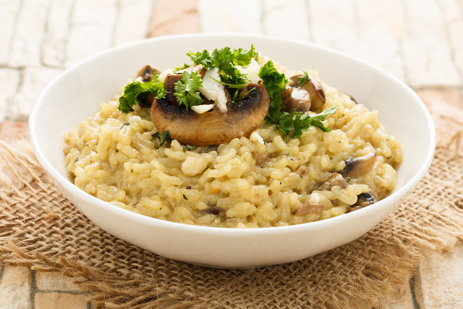 Mushroom risotto with fresh herbs, Parmesan cheese and a bunch of mushrooms on top of it, in a white bowl.