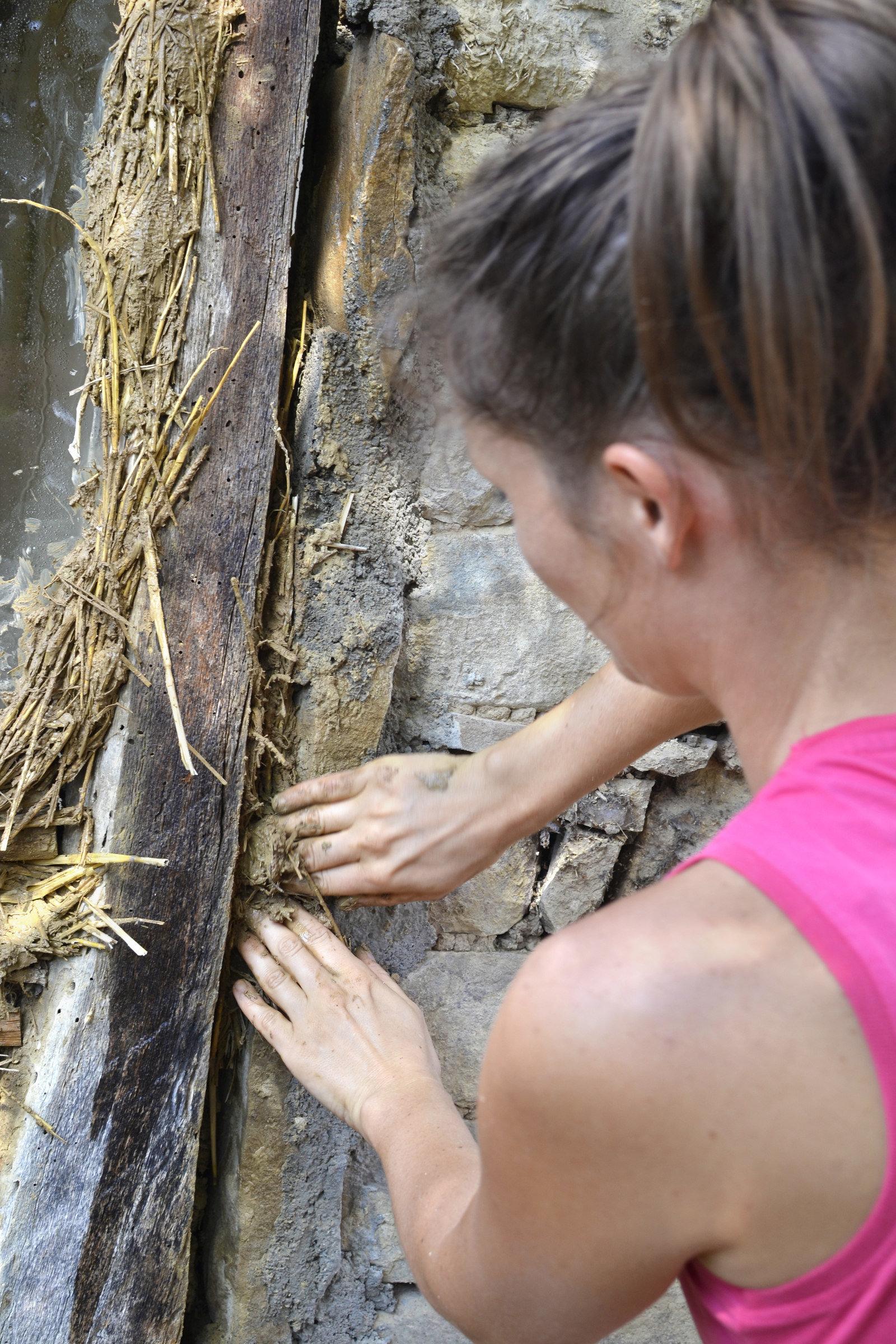 A woman pressing cob materials into gap on home