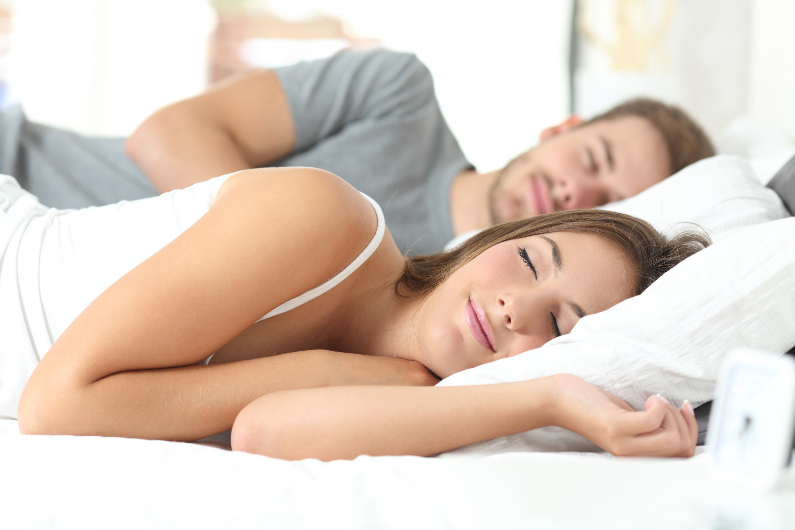 man and woman sleeping comfortably in bed