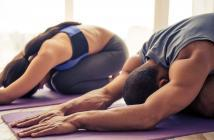 couple doing yoga pose on mat in home