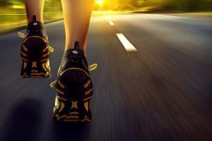 person running down road for aerobic exerise