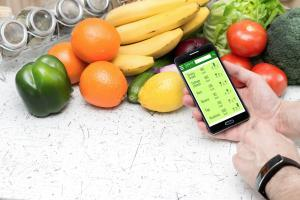 fresh fruits and vegetables with smartphone and caloria tracker