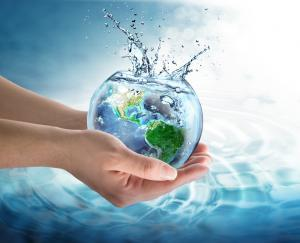 pair of hands holding glass bowl with earth's continents and water