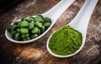 spoons with spirulina supplements and powder