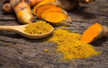 sliced turmeric root and powdered turmeric on a wooden spoon