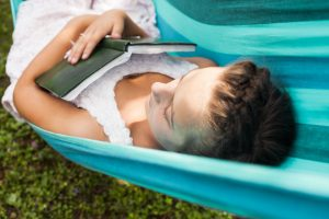 woman sleeping in hammock with book