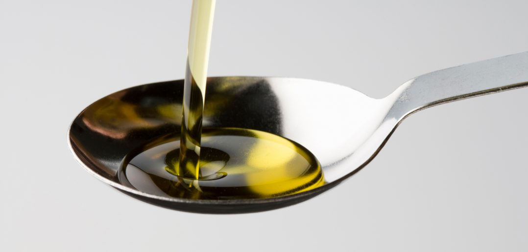 castor oil pouring into a spoon