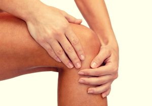 massaging castor oil into sore knee joint