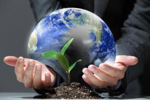 man holding planet earth with plant growing