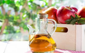 apple cider vinegar beside basket of apples