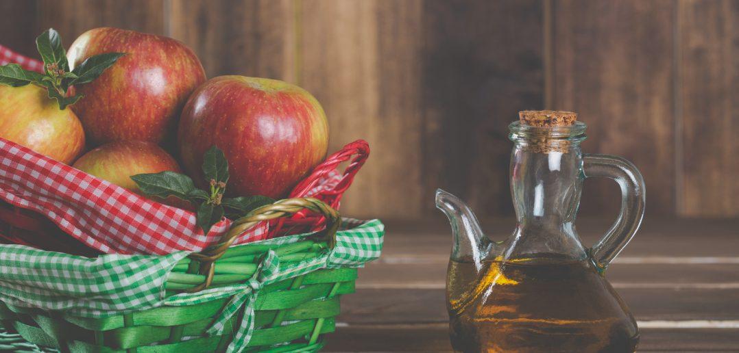 bottle of apple cider vinegar beside a basket of apples (for article about apple cider vinegar uses)