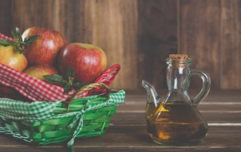 bottle of apple cider vinegar beside a basket of apples (for article about apple cider vinegar uses)