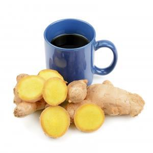ginger root in front of cup of ginger tea