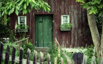 front door of homestead with plants and picket fence